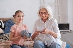 Fille assez jeune aidant sa grand-mère Image stock