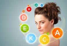 Fille assez jeune avec les icônes et les symboles colorés de vitamine Image libre de droits