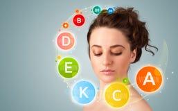 Fille assez jeune avec les icônes et les symboles colorés de vitamine Photos stock