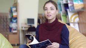 Fille assez jeune d'université regardant par une magazine et pensant à quelque chose bonne clips vidéos