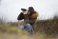 Fille assez jeune/femme observant par le télescope t d'ornitology Images libres de droits