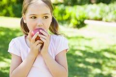 Fille assez jeune mangeant la pomme en parc photo stock