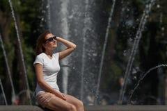 Fille assez jeune s'asseyant dans des lunettes de soleil sur le fond de fontaine Photographie stock