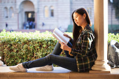 Fille assez jeune s'asseyant sur la fenêtre au terrac d'université Images libres de droits