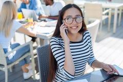 Fille assez millénaire parlant avec l'ami au téléphone Image libre de droits