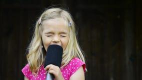 Fille assez petite avec le chant de microphone clips vidéos