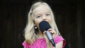 Fille assez petite avec le chant de microphone banque de vidéos