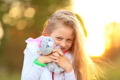 Fille assez petite avec un jouet mou préféré en parc Photographie stock libre de droits