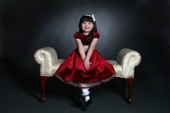 Fille assez petite dans la robe rouge de vacances Photos libres de droits