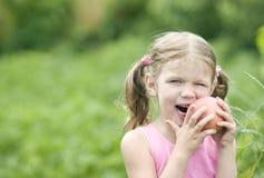 Fille assez petite mangeant un Apple. Images libres de droits