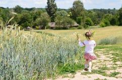 Fille assez petite marchant loin sur la route rurale Photographie stock libre de droits