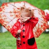 Fille assez petite triste dans l'imperméable rouge avec le parapluie marchant en été de parc Photo stock