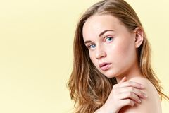 Fille assez rousse d'adolescent avec des yeux bleus et des taches de rousseur, avec les épaules nues, regardant l'appareil-photo  Photographie stock