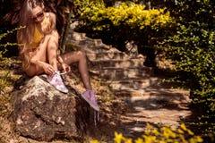 Fille assez sportive dans un knit sexy de bikini jaune sur le footpat Image libre de droits