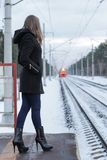 Fille attendant un train sur la gare ferroviaire Photo libre de droits