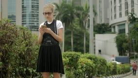 Fille attirante à l'aide du téléphone portable pour trouver une adresse avec un navigateur de généralistes banque de vidéos