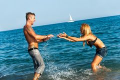 Fille attirante éclaboussant son ami sur la plage. Image libre de droits