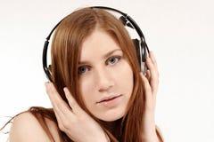 Fille attirante avec des écouteurs photo stock