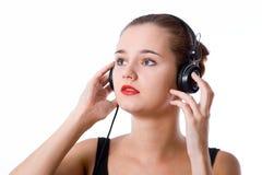 Fille attirante avec des écouteurs sur le fond blanc photographie stock libre de droits