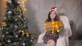 Fille attirante avec des présents donnant le cadeau dans l'appareil-photo près de l'arbre de Noël clips vidéos