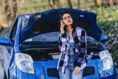 fille attirante avec le capot ouvert proche de téléphone de la voiture image stock