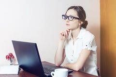 Fille attirante avec les verres dactylographiant sur un ordinateur portable photographie stock libre de droits