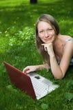 Fille attirante avec un ordinateur portatif en stationnement Photographie stock libre de droits