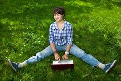 Fille attirante avec un ordinateur portatif en stationnement Image libre de droits