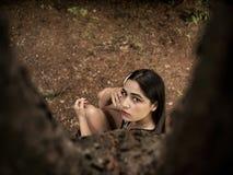 Fille attirante d'aspect caucasien s'asseyant près d'un arbre, tenant une main près du visage Vue de ci-avant photographie stock libre de droits