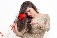 Fille attirante de cheveux bouclés avec la baguette magique rougeoyante de cupidon Photo libre de droits
