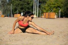 Fille attirante de forme physique dans des lunettes de soleil s'étendant à la plage pendant le matin L'espace vide photos libres de droits