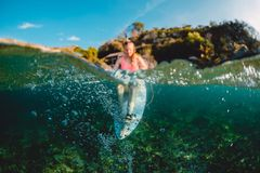 Fille attirante de surfer avec la planche de surf Le surfer s'asseyent au conseil photos stock