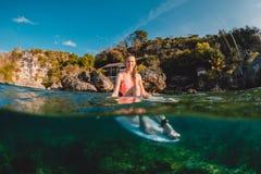 Fille attirante de surfer avec la planche de surf Le surfer s'asseyent au conseil images stock