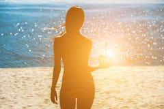 Fille attirante et jeune tenant une noix de coco pour boire tout en détendant à une station de vacances près de l'océan images libres de droits