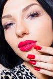 Fille attirante, jeune femme beuatiful de tentation de brune avec des yeux bleus, longues mèches, rouge à lèvres rouge et clous r Images stock