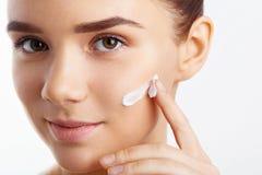 Fille attirante mettant la crème anti-vieillissement sur son visage Portrait de fille avec la peau lisse saine photographie stock libre de droits