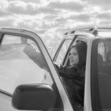 fille attirante noire et blanche dans la voiture dans le siège de passager Photo stock