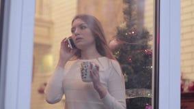 Fille attirante parlant au téléphone près de la fenêtre banque de vidéos