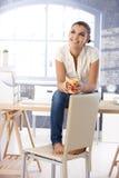 Fille attirante rêvassant sur le sourire de bureau Image stock