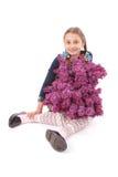 Fille attirante s'asseyant sur le plancher blanc avec le lilas à disposition Photographie stock libre de droits