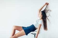 Fille attirante se trouvant sur la chaise, jouant des cheveux, heureux Photos libres de droits