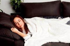 Fille attirante se trouvant sur le divan couvert de couverture Photo stock