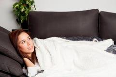 Fille attirante se trouvant sur le divan couvert de couverture Image stock