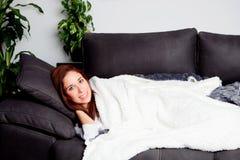 Fille attirante se trouvant sur le divan couvert de couverture Photographie stock libre de droits