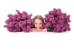 Fille attirante se trouvant sur le plancher blanc avec le lilas à disposition Photographie stock