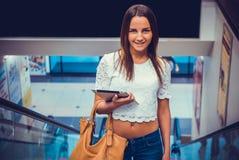 Fille attirante tenant le comprimé argenté d'ordinateur Image stock