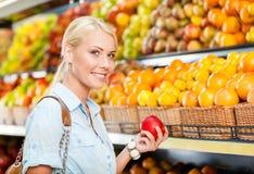 Fille au centre commercial choisissant la pomme de mains de fruits Image stock