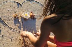 Fille au coeur de dessin de plage sur le sable Image stock