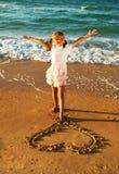 Fille au coeur de dessin de plage sur un sable Image libre de droits