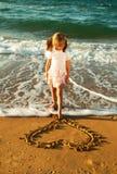 Fille au coeur de dessin de plage sur un sable Photo stock